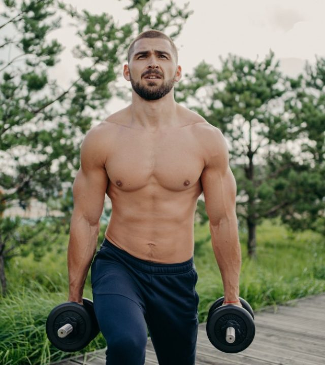 sport-and-recreation-concept-muscular-unshaven-sporty-man-holds-heavy-barbells-in-hands-poses-with_t20_vLb91z